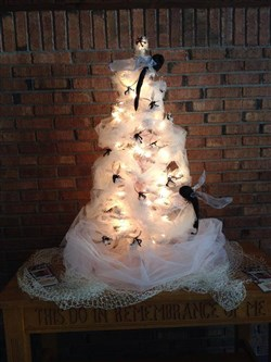 Lighted tabletop tree covered by net and mosquitoes